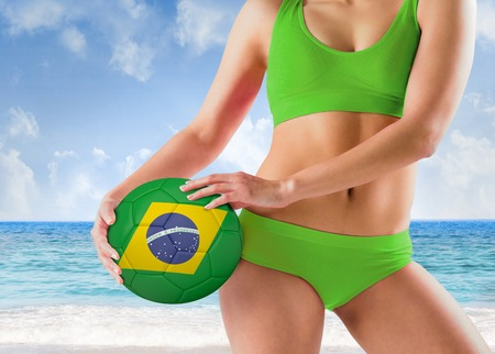 Composite image of fit girl in green bikini holding brasil ball against beach scene photo
