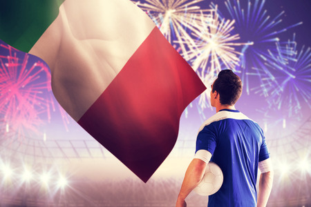 Handsome italian football player in blue jersey against fireworks exploding over football stadium photo