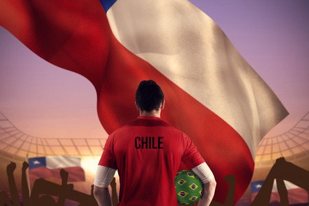 Chile football player holding ball against large football stadium under purple sky photo