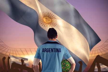 Argentina football player holding ball against large football stadium under purple sky photo