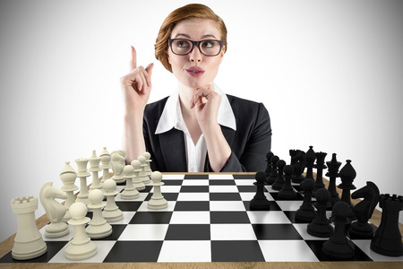 Composite image of thinking redhead businesswoman with chessboard photo