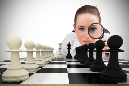 Composite image of thinking businesswoman with magnifying glass with chessboard Stock Photo - 29047524