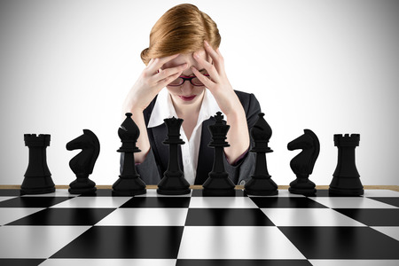 pawn adult: Composite image of redhead businesswoman with head in hands with chessboard