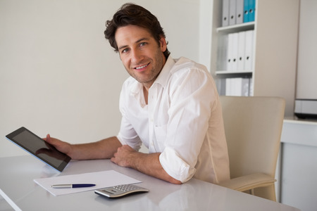 Casual smiling businessman using tablet and calculator in his office photo