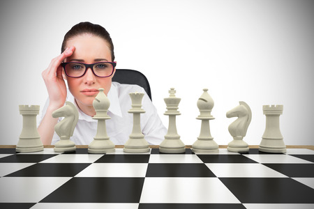 pawn adult: Composite image of thinking businesswoman with chessboard Stock Photo