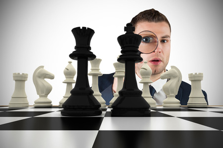 Composite image of businessman looking through magnifying glass with chessboard Stock Photo - 29047428