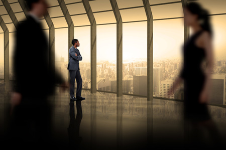 Business people walking in a blur against room with large window looking on city photo