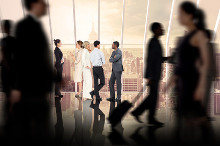 Business colleagues talking against room with large window looking on city photo