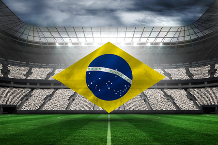 Digitally generated brazilian national flag against football stadium with fans in white photo