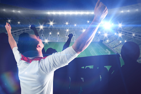 Excited football fan cheering against large football stadium with lights photo
