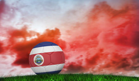 Football in costa rica colours against green grass under red cloudy sky photo