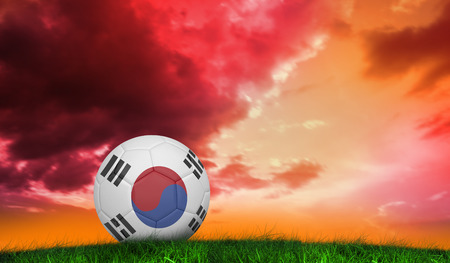 Football in south korea colours  against green grass under red and purple sky photo