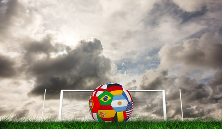 multi national: Football in multi national colours against green grass under grey sky Stock Photo