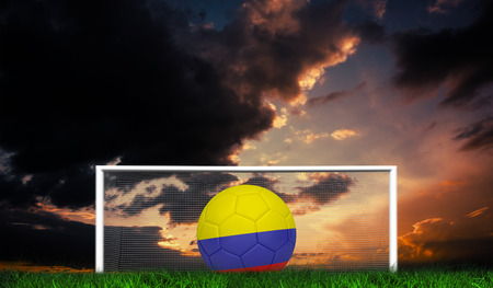 Football in colombia colours against green grass under dark blue and orange sky photo