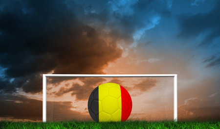 Football in germany colours against green grass under blue and orange sky photo
