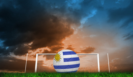 Football in uruguay colours  against green grass under blue and orange sky photo