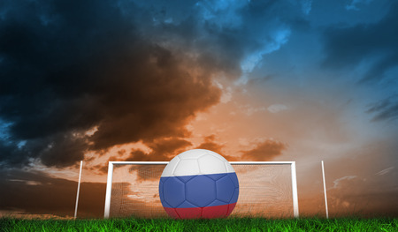 Football in russia colours against green grass under blue and orange sky photo
