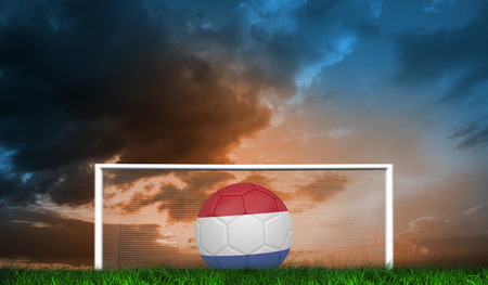 Football in holland colours against green grass under blue and orange sky photo