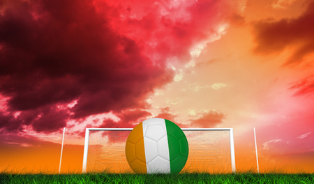 Football in ivory Coast colours against green grass under red and purple sky photo