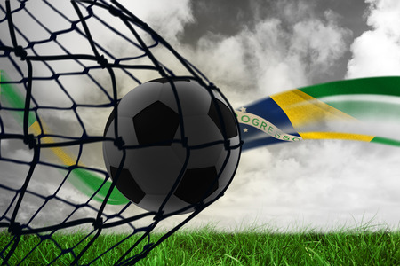 against the flow: Composite image of football in back of the net against brazilian flag flow