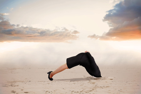 burying: Businesswoman burying her head against misty landscape Stock Photo