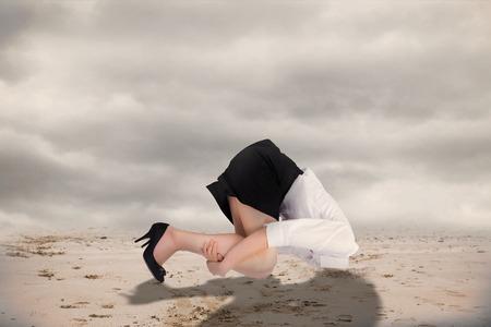 burying: Businesswoman burying her head against misty desert landscape