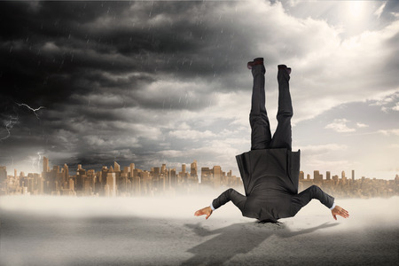 burying: Businessman burying his head against large city on the horizon