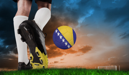Composite image of football boot kicking bosnia ball against green grass under blue and orange sky photo