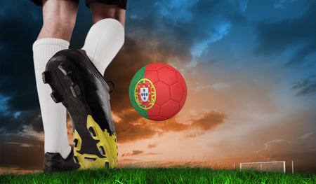 Composite image of football boot kicking spain ball against green grass under blue and orange sky photo