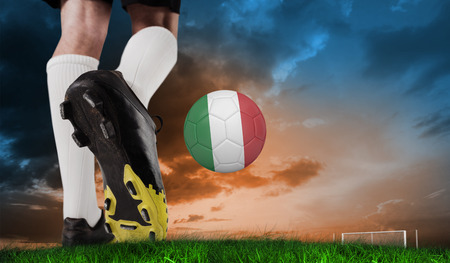Composite image of football boot kicking italy ball against green grass under blue and orange sky photo