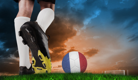 Composite image of football boot kicking france ball against green grass under blue and orange sky photo