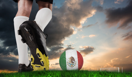 Composite image of football boot kicking mexico ball against green grass under blue and orange sky photo