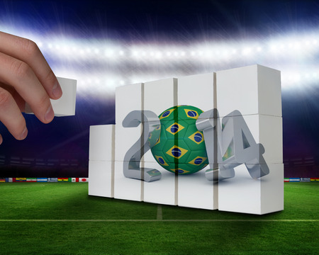 Hand building wall against football pitch with world cup flags photo