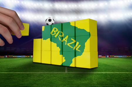 Hand building wall of green brazil outline on yellow with text photo
