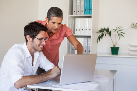 Casual business team working together at desk using laptop in the office photo