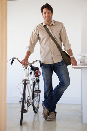 businessman standing: Casual businessman standing with his bike smiling at camera in the office Stock Photo