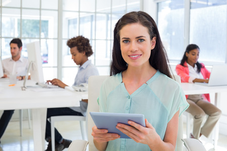 Attractive businesswoman with tablet pc in the office photo