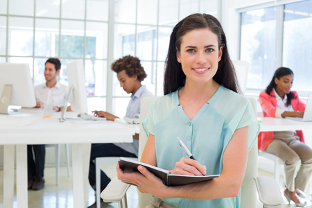 Attractive businesswoman writing in notebook and smiling to camera in the office photo