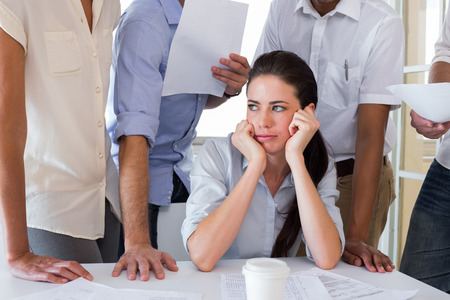 Worried businesswoman surrounded by colleagues in the office photo