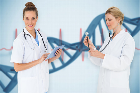 Composite image of female medical team against blue medical background with dna and ecg photo
