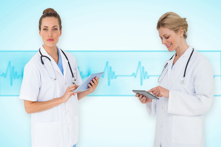 Composite image of female medical team against medical background with blue ecg line photo
