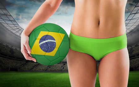 Fit girl in green bikini holding brazil football against large football stadium with lights photo