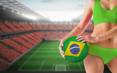Fit girl in green bikini holding brasil ball against vast football stadium with fans in red photo