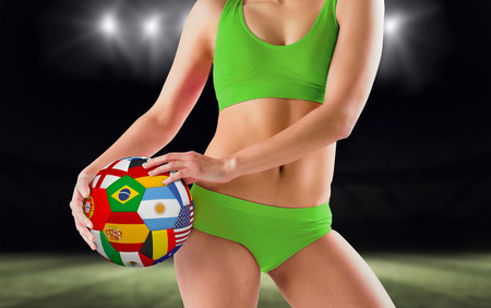 Fit girl in green bikini holding flag ball against football pitch at night with lights photo