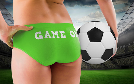 Fit girl in green bikini holding football  against large football stadium with lights photo