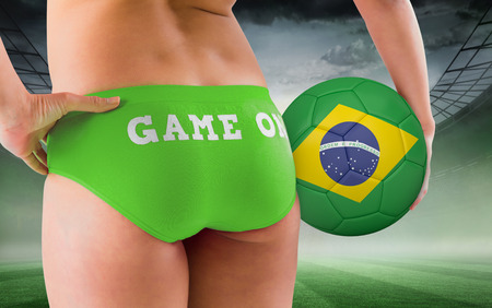 Fit girl holding brasil ball against misty football stadium under spotlights photo