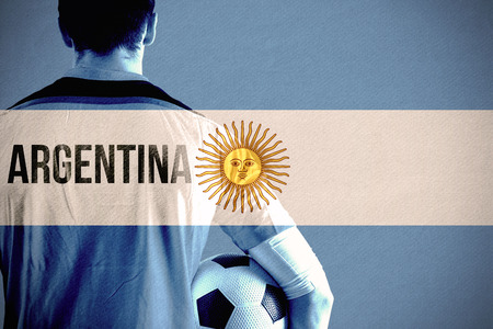 Argentina football player holding ball against argentina national flag photo