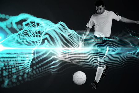 Football player in white kicking against abstract blue glowing black background photo