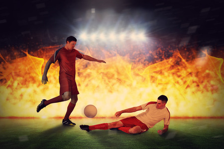 Football players tackling for the ball against football pitch under spotlights Stock Photo - 29046891