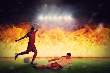 Football players tackling for the ball against football pitch under spotlights Stock Photo - 29046895